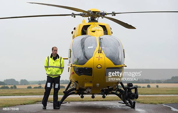Britain's Prince William The Duke of Cambridge poses by an air ambulance he begins his new job with the East Anglian Air Ambulance at Cambridge...