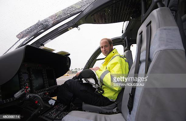 Britain's Prince William The Duke of Cambridge poses in the cockpit of a helicopter air ambulance he begins his new job with the East Anglian Air...