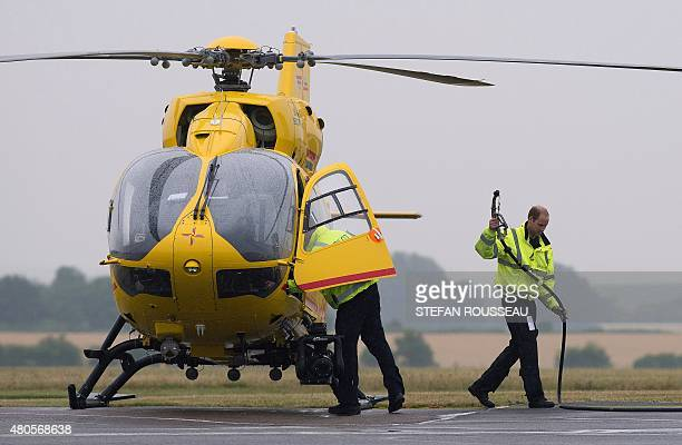 Britain's Prince William The Duke of Cambridge refuels a helicopter as he begins his new job with the East Anglian Air Ambulance at Cambridge Airport...