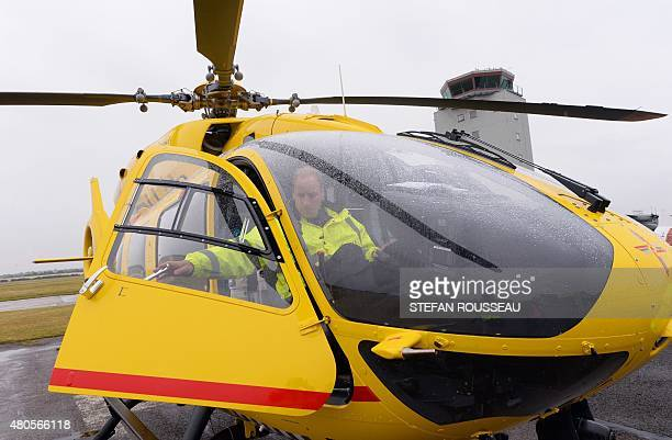 Britain's Prince William The Duke of Cambridge sits in the cockpit of a helicopter air ambulance he begins his new job with the East Anglian Air...