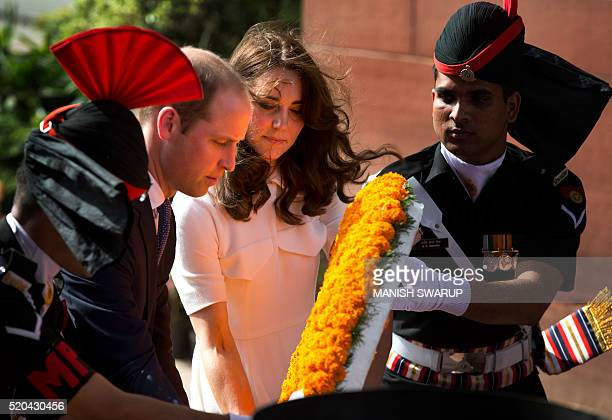Britain's Prince WilliamDuke of Cambridgealong with his wife Catherine Duchess of Cambridge are assisted by Indian soldiers as they lay a wreath as...