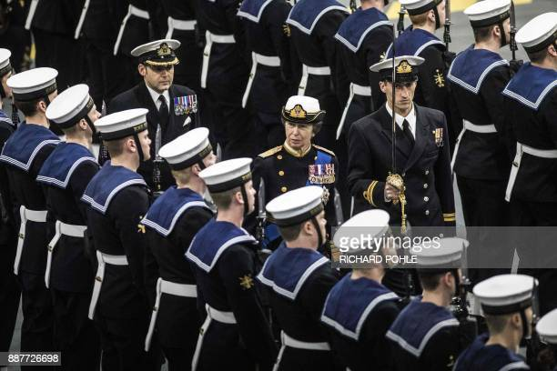 TOPSHOT Britain's Princess Anne Princess Royal inspects a naval guard of honor during the Commissioning Ceremony for the Royal Navy aircraft carrier...