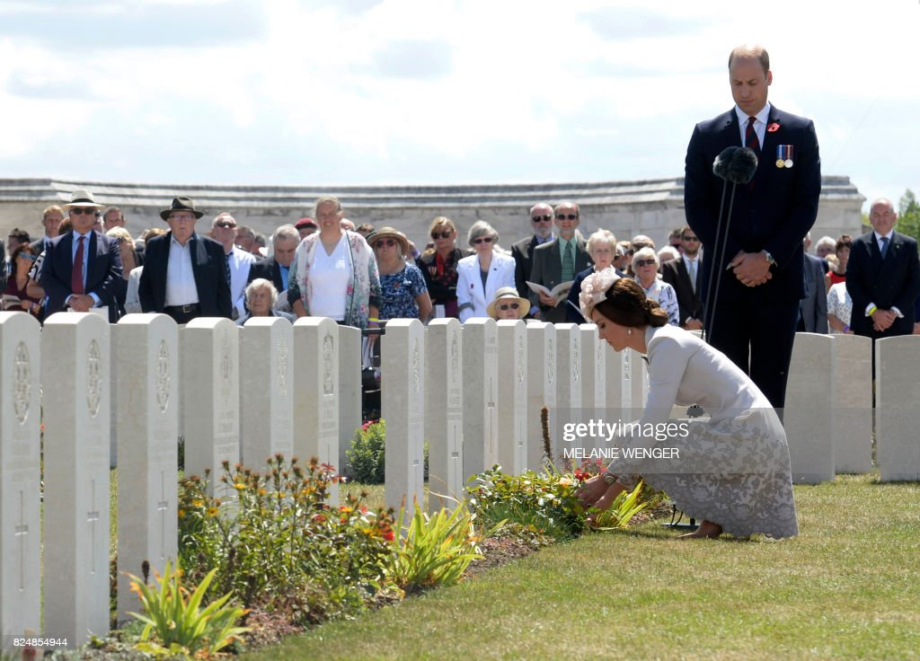 TOPSHOT - Britain's Princess Catherine, Duchess of Cambridge, and Britain's Prince William, Duke of Cambridge, lay flowers at the headstones of soldiers who fell in World War One at The Tyne Cot Commonwealth War Graves Cemetery in Zonnebeke on July 31, 2017, as part of a series of commemorations for the 100th anniversary of the Battle of Passchendaele. The battle of Passchendaele, also called the third battle of Ypres, took place between July 31 and November 6, 1917 in Passendale, West Flanders. / AFP PHOTO / POOL / Melanie Wenger
