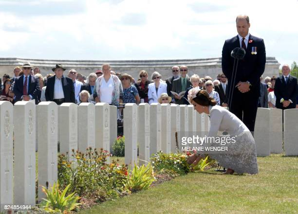 TOPSHOT Britain's Princess Catherine Duchess of Cambridge and Britain's Prince William Duke of Cambridge lay flowers at the headstones of soldiers...
