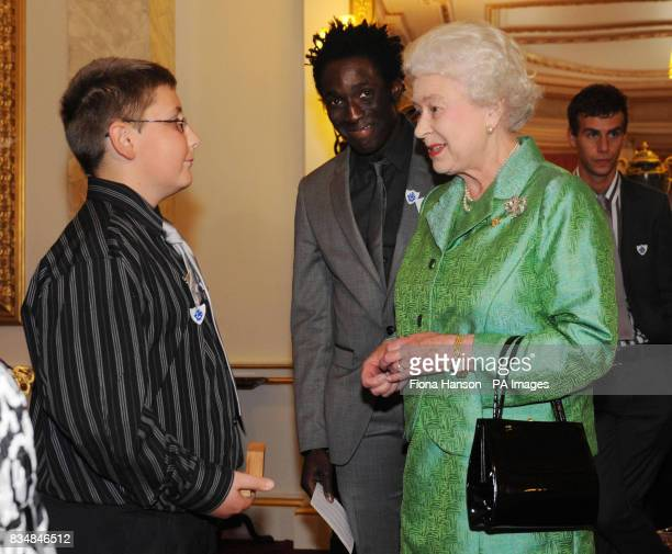 Britain's Queen Elizabeth II accompanied by current Blue Peter presenter Andy Akinwolere presents a gold Blue Peter badge to Iestyn Davies from Wales...