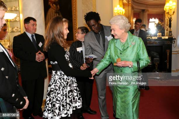 Britain's Queen Elizabeth II accompanied by current Blue Peter presenter Andy Akinwolere presents a gold Blue Peter badge to Dani Jacobsen from...