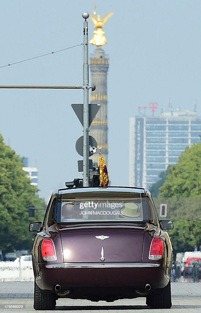 Britain's Queen Elizabeth II and Britain's Prince Philip, Duke of Edinburgh drive through Berlin's landmark Brandenburg Gate in a car on June 26, 2015, as they leave Berlin. British Queen Elizabeth II ends her three-day visit to Germany.