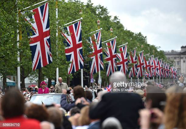 TOPSHOT Britain's Queen Elizabeth II and Britain's Prince Philip Duke of Edinburgh wave to guests as they visit the Patron's Lunch a special street...