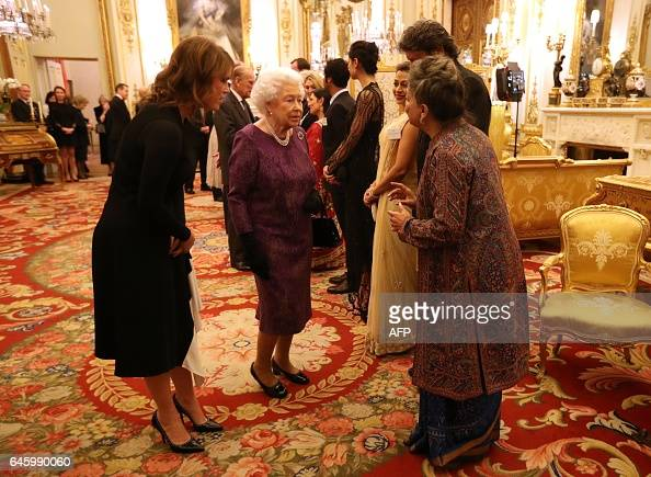 Britain's Queen Elizabeth II and Britain's Princess Eugenie of York greet Aloka Mitra the founder of Women's Interlink Foundation during a reception...