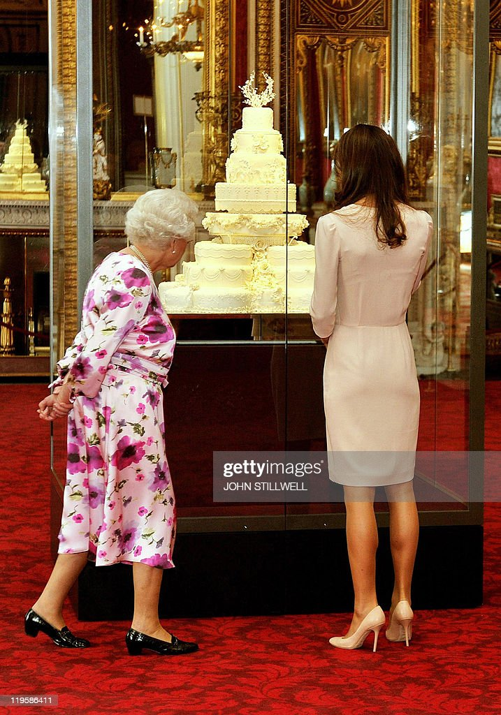 Britain's Queen Elizabeth II (L) and Catherine, the Duchess of Cambridge view a glass cabinet containing the royal wedding cake made for her marriage to Britain's Prince William at the annual summer exhibition at Buckingham Palace in central London, on July 22, 2011. Britain's Queen Elizabeth II has reportedly described as 'creepy' a new exhibition featuring the wedding dress worn by the former Kate Middleton when she married Prince William in April. The Alexander McQueen dress is being exhibited on a headless mannequin in the ballroom at Buckingham Palace, with the tiara and veil that the now Duchess of Cambridge wore, suspended above it. AFP PHOTO / JOHN STILLWELL / WPA POOL