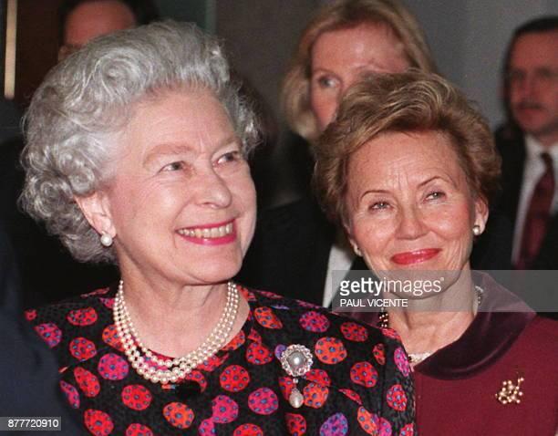 Britain's Queen Elizabeth II and Eeva Ahtisaari wife of Finnish President Marrti Ahtisaari smile as they look at exibits 25 November during a visit...