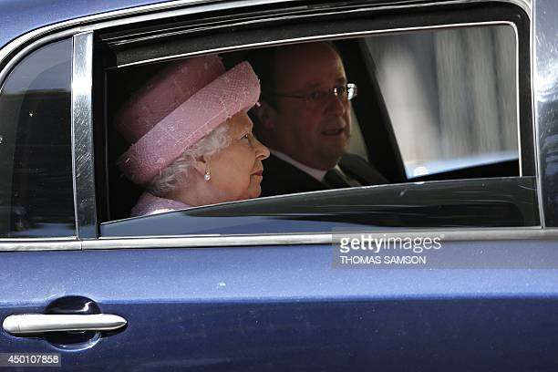 Britain's Queen Elizabeth II and French President Francois Hollande sit in the President's car as they drive down the ChampsElysees avenue in Paris...