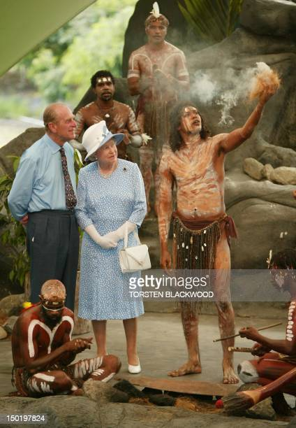 Queen Elizabeth II and her husband Prince Philip watch Tjapukai Aborigines light a ceremonial fire during a cultural performance near Cairns 01 March...