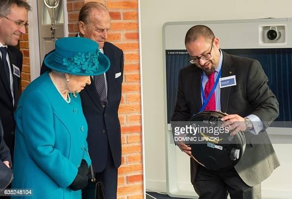 Britain's Queen Elizabeth II and her husband Britain's Prince Philip Duke of Edinburgh listen as Technical Director Ian Levy explains how a robotic...