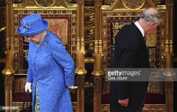 TOPSHOT Britain's Queen Elizabeth II and her son Britain's Prince Charles Prince of Wales prepare to take their seats as they arrive in the House of...