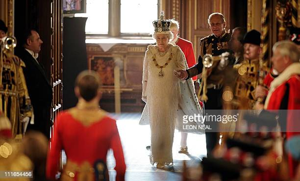 Britain's Queen Elizabeth II and Prince Philip walk through the Royal Gallery of the House of Lords in Westminster in London 06 November 2007 during...