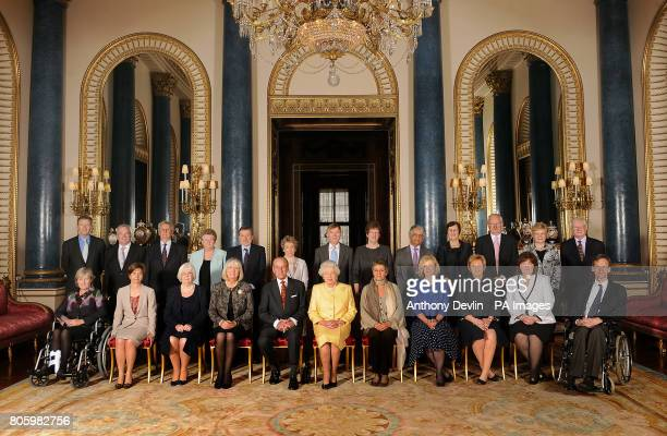 Britain's Queen Elizabeth II and the Duke of Edinburgh pose with Civil Service Commissioners before a reception at Buckingham Palace London They are...