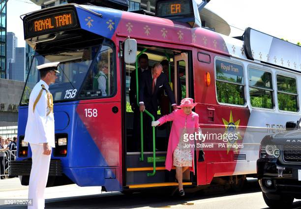 Britain's Queen Elizabeth II and the Duke of Edinburgh step off of an electric tram after riding through the Melbourne city centre past huge crowds...