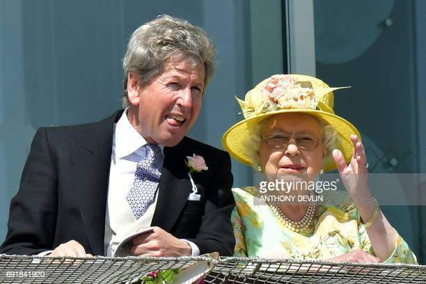 Britain's Queen Elizabeth II and the Queen's racing manager John Warren watch the racing on the second day of the Epsom Derby Festival in Surrey...