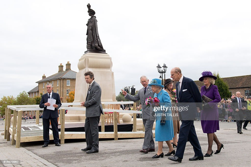 Britain's Queen Elizabeth II (3R), Britain's Prince Charles, Prince of Wales (4R), Britain's Prince Philip, Duke of Edinburgh (2R) and Britain's Camilla, Duchess of Cornwall (R) leave after unveiling a statue of the Queen Elizabeth The Queen Mother in the square on a visit to the town of Poundbury, southwest England, on October 27, 2016. The Queen and The Duke of Edinburgh, accompanied by The Prince of Wales and The Duchess of Cornwall, visited Poundbury. Poundbury is an experimental new town on the outskirts of Dorchester in southwest England designed by Leon Krier with traditional urban principles championed by The Prince of Wales and built on land owned by the Duchy of Cornwall. / AFP / POOL / JUSTIN