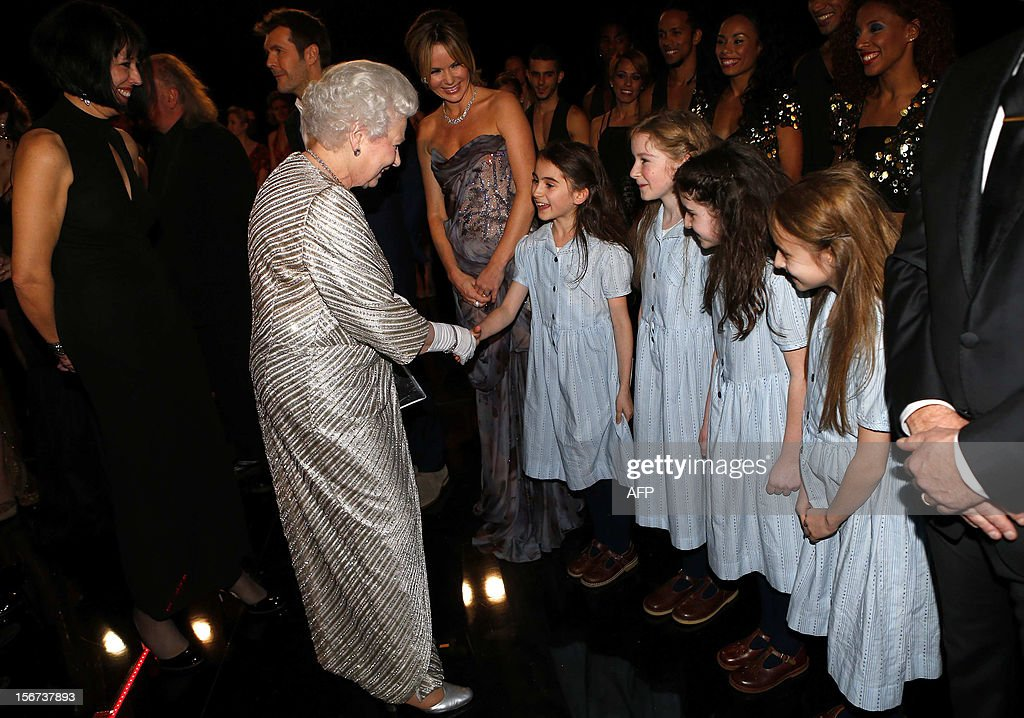Britain's Queen Elizabeth II (L) child performers from the musical 'Matilda' after the Royal Variety Performance at the Royal Albert Hall in London on November 19, 2012. The Queen, accompanied by The Duke of Edinburgh, attended the Royal Variety Performance in the show's 100th anniversary year where she met with stars of the show including Kylie Minogue, tenor Andrea Bocelli and the performing dog Pudsey. AFP PHOTO / POOL / ANDREW WINNING