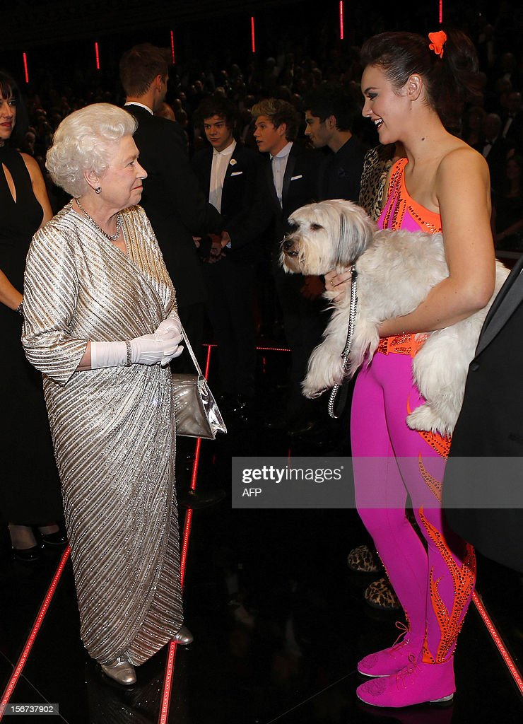 Britain's Queen Elizabeth II (L) greets Ashleigh and her performing dog Pudsey after the Royal Variety Performance at the Royal Albert Hall in London on November 19, 2012. The Queen, accompanied by The Duke of Edinburgh, attended the Royal Variety Performance in the show's 100th anniversary year where she met with stars of the show including Kylie Minogue, tenor Andrea Bocelli and the performing dog Pudsey.