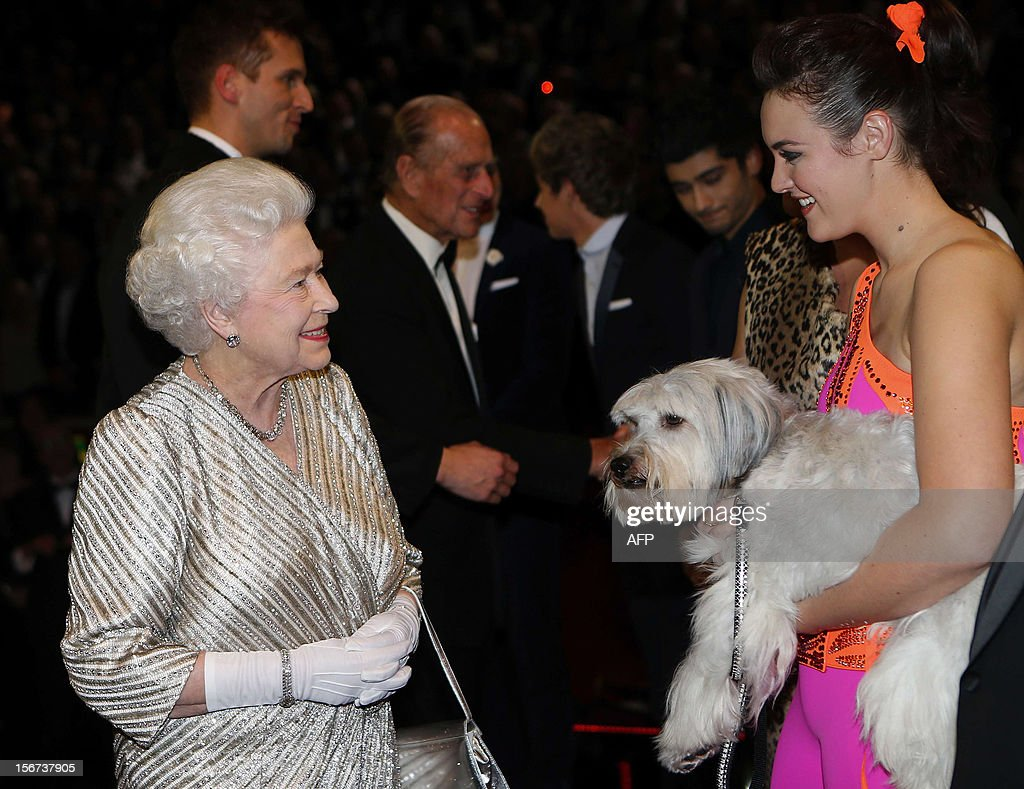 Britain's Queen Elizabeth II (L) greets Ashleigh and her performing dog Pudsey after the Royal Variety Performance at the Royal Albert Hall in London on November 19, 2012. The Queen, accompanied by The Duke of Edinburgh, attended the Royal Variety Performance in the show's 100th anniversary year where she met with stars of the show including Kylie Minogue, tenor Andrea Bocelli and the performing dog Pudsey. AFP PHOTO / POOL / ANDREW WINNING