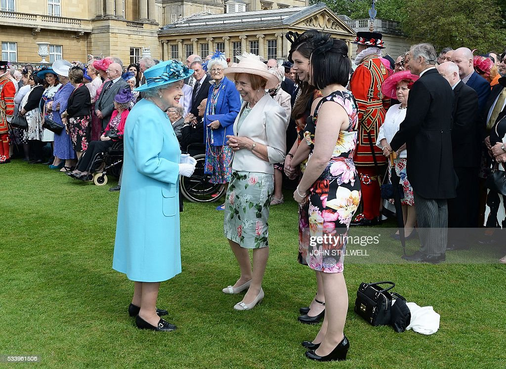Britain's Queen Elizabeth II (L) greets guests attending a garden party at Buckingham Palace in London on May 24, 2016. / AFP / POOL / John Stillwell