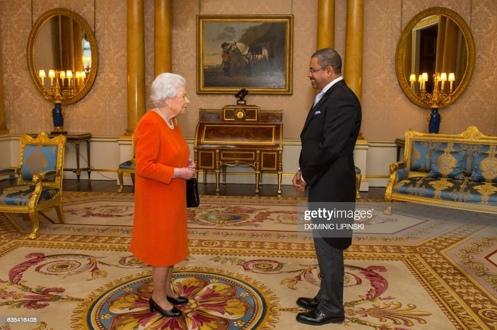 Britain's Queen Elizabeth II (L) greets Republic of Seychelles Ambassador, Derick Ally, during a private audience at Buckingham Palace in London on February 15, 2017. / AFP / POOL / Dominic Lipinski