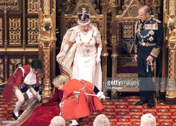 Britain's Queen Elizabeth II has her robe's train adjusted bu young pageboys on her entrance to the State Opening of Parliament 17 November 1999 in...