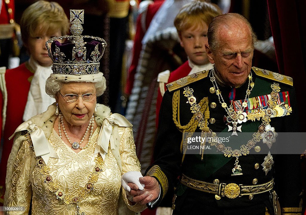 Britain's Queen Elizabeth II holds the hand of her husband Prince Philip, as she arrives to address to the House of Lords, during the State Opening of Parliament in Westminster, central London on May 25, 2010. Britain's Queen Elizabeth II set out the new coalition government's legislative programme on Tuesday in a ceremony of pomp and history following the closest general election for decades. AFP PHOTO/Leon Neal/Pool