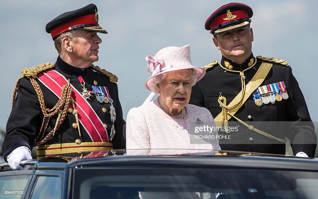 Britain's Queen Elizabeth II (C), in her role as Captain-General of The Royal Regiment of Artillery, stands in the State Review Range Rover as she reviews the weapons of the Royal Artillery at Knighton Down, Larkhill on Salisbury plain, souther England on May 26, 2016. 2016 marks the Tercentenary of the formation of the Royal Artillery when, on 26 May 1716, by Royal Warrant of King George 1, two companies of artillery were formed at Woolwich in London, alongside the guns, powder and shot located in the Royal Arsenal. / AFP / RICHARD