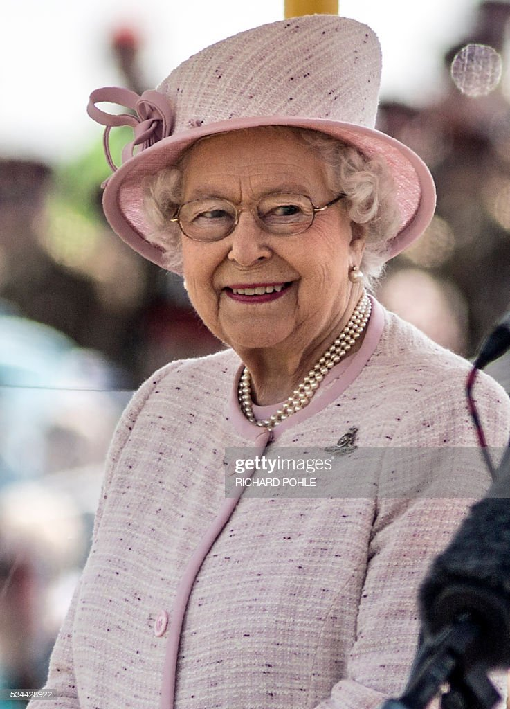 Britain's Queen Elizabeth II, in her role as Captain-General of The Royal Regiment of Artillery, reacts as she watches the Kings Troop Royal Horse Artillery ride past during her review of the weapons of the Royal Artillery at Knighton Down, Larkhill on Salisbury plain, souther England on May 26, 2016. 2016 marks the Tercentenary of the formation of the Royal Artillery when, on 26 May 1716, by Royal Warrant of King George 1, two companies of artillery were formed at Woolwich in London, alongside the guns, powder and shot located in the Royal Arsenal. / AFP / RICHARD
