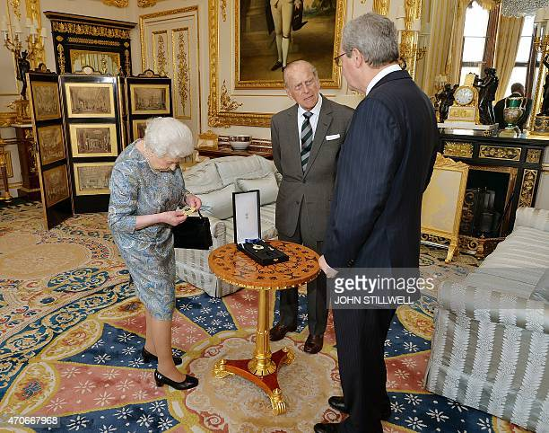 Britain's Queen Elizabeth II inspects the Insignia of a Knight of the Order of Australia after presenting it to her husband Prince Philip Duke of...