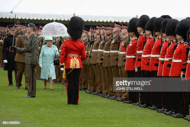 TOPSHOT Britain's Queen Elizabeth II inspects the Regiment during a ceremony to present new colours to the 1st Battalion and F Company Scots Guards...
