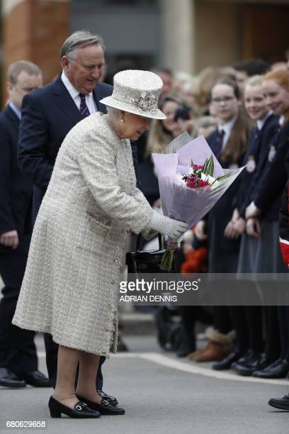 Britain's Queen Elizabeth II is accompanied by Chair of Governors Roger Laneknott during her visit to Pangbourne College in Berkshire County on May 9...