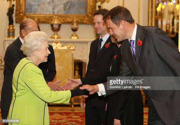 Britain's Queen Elizabeth II is greeted by Deputy Prime Minister Nick Clegg and Entrepreneur Peter Jones at the annual Civil Service Awards Reception...