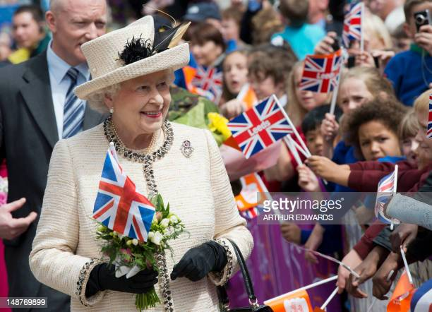 Britain's Queen Elizabeth II is greeted by flagwaving wellwishers as she visits the City Varieties Music Hall in Leeds West Yorkshire northern...