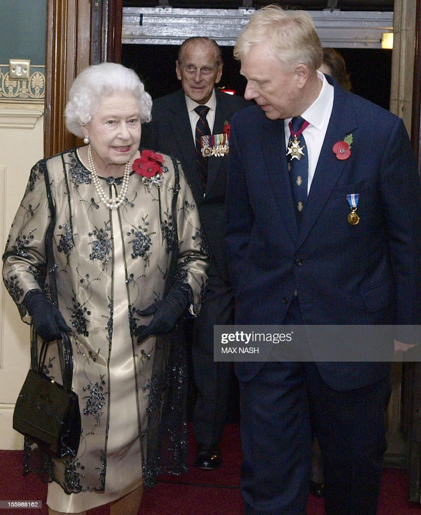Britain's Queen Elizabeth II (L) is greeted by the President of the Royal British Legion Vice- Admiral Peter Wilkinson (R) as she arrives to attend the annual Royal Festival of Remembrance, at London's Royal Albert Hall, November 10, 2012. Prince Philip, the Duke Of Edinburgh (2nd L) follows behind.
