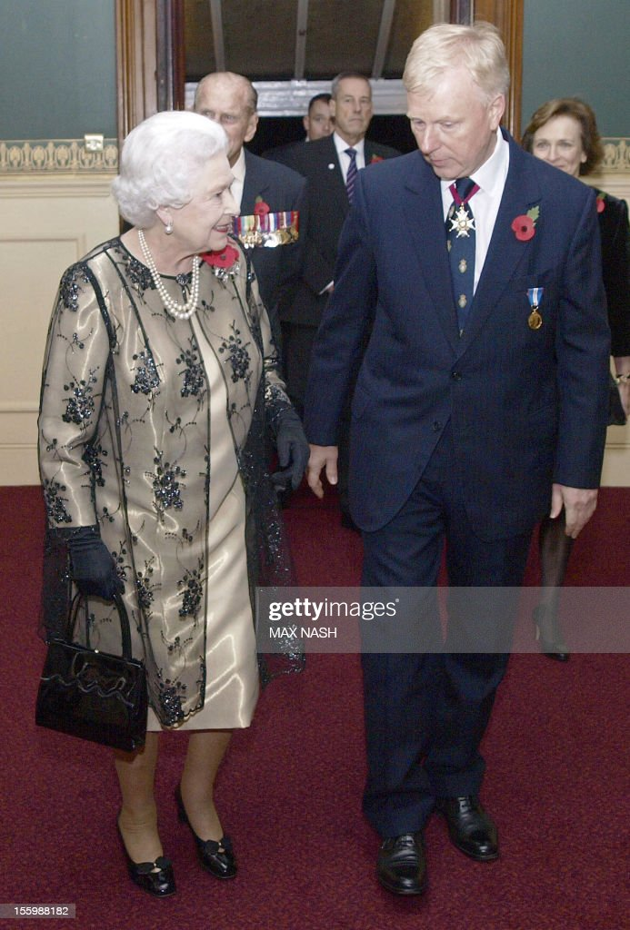 Britain's Queen Elizabeth II (L) is greeted by the President of the Royal British Legion Vice- Admiral Peter Wilkinson (R) as she arrives to attend the annual Royal Festival of Remembrance, at London's Royal Albert Hall, November 10, 2012.