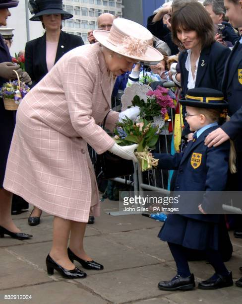 Britain's Queen Elizabeth II is presented with flowers as she begins a walkabout from Manchester Cathedral today following the traditional Royal...
