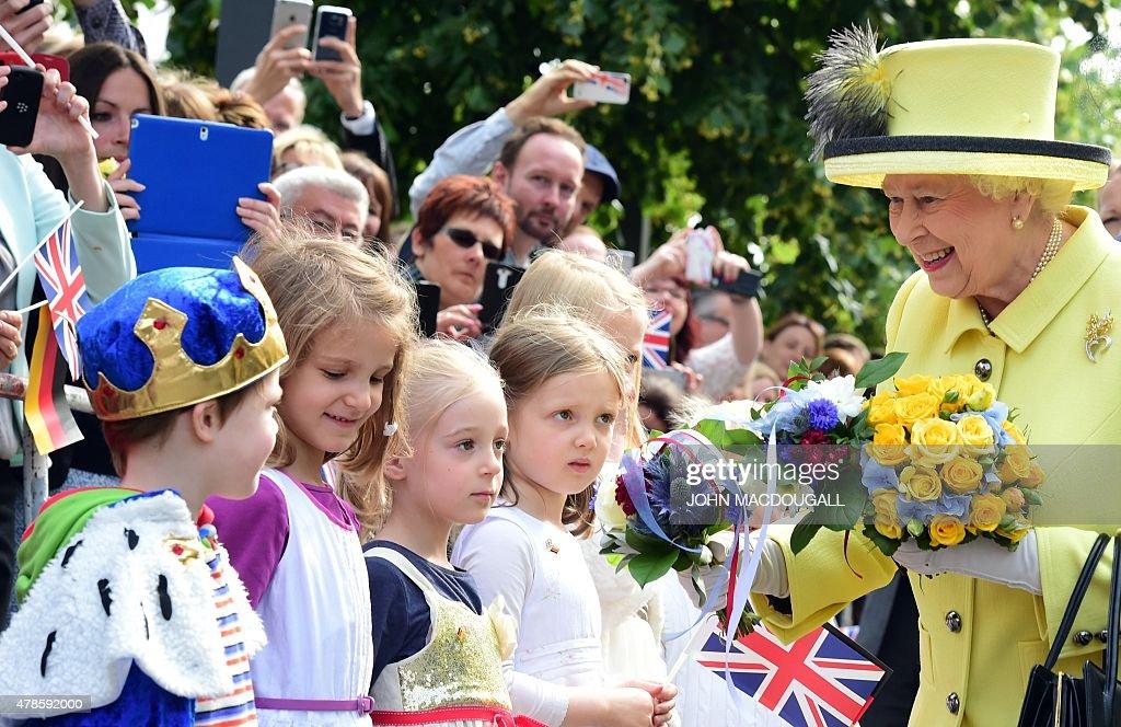 Britain's Queen Elizabeth II (R) is presented with flowers as she walks across the Pariser Platz near Berlin's landmark Brandenburg Gate on June 26, 2015, on her way to leave Berlin. British Queen Elizabeth II ends her three-day visit to Germany.