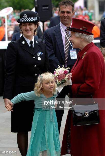 Britain's Queen Elizabeth II is presented with flowers by Lydia Beshenivsky five the daughter of murdered WPC Sharon Beshenivsky during her visit to...