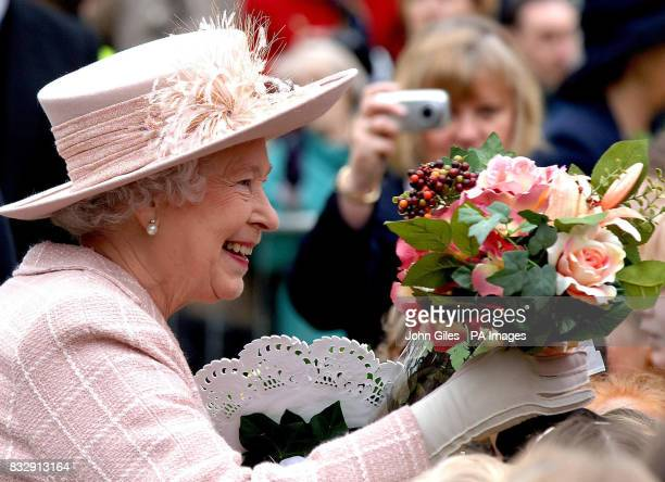 Britain's Queen Elizabeth II is presented with flowers during a walkabout outside Manchester Cathedral today following the traditional Royal Maundy...