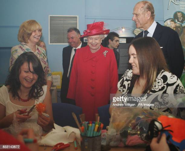 Britain's Queen Elizabeth II is shown a doll of Prince Harry by Caroline Milne during a tour The Shore where she met young people staff and volunteers