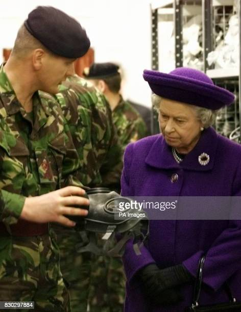 Britain's Queen Elizabeth II is shown a gas mask by a reservist in the Quartermaster's store at Chetwynd Barracks Chilwell Nottingham