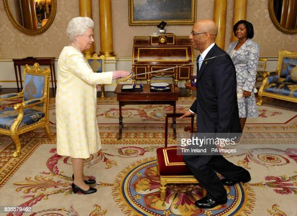 Britain's Queen Elizabeth II knights GovernorGeneral of Jamaica Sir Patrick Allen accompanied by his wife Patricia where he was presented his...