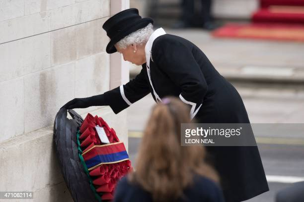 Britain's Queen Elizabeth II lays a wreath during a service to commemorate ANZAC day and the centenary of the Battle of Gallipoli at the Cenotaph war...