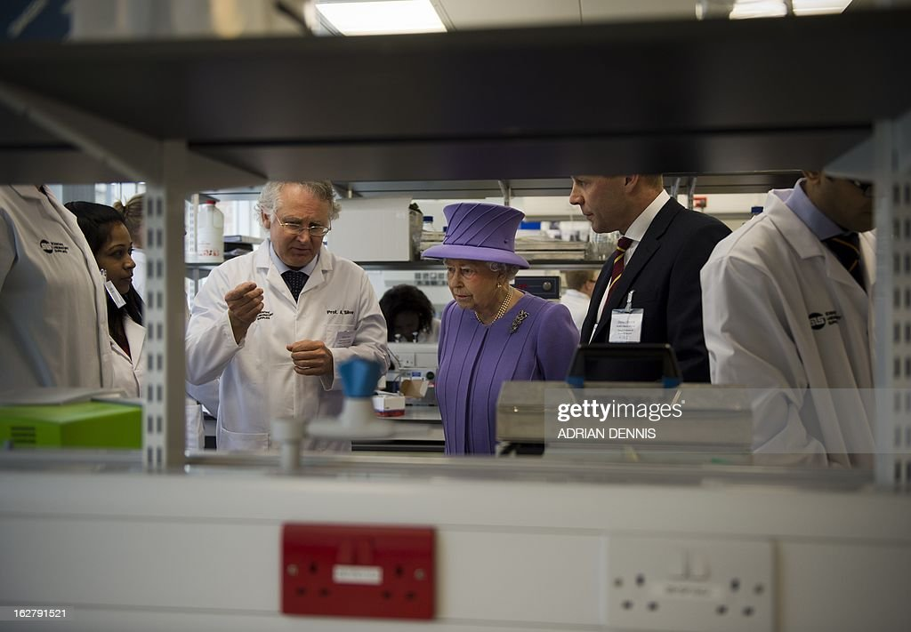 Britain's Queen Elizabeth II (C) listens to Professor Andrew Silver (L) during a visit to the new National Centre for Bowel Research and Surgical Innovation in London on February 27, 2013. The Queen accompanied by the Duke of Edinburgh toured the new Royal London Hospital building, visiting the new Children's Services area meeting patients and staff. They also visited the new National Centre for Bowel Research and Surgical Innovation where they toured state-of-the-art laboratories dedicated to the study of human tissue.