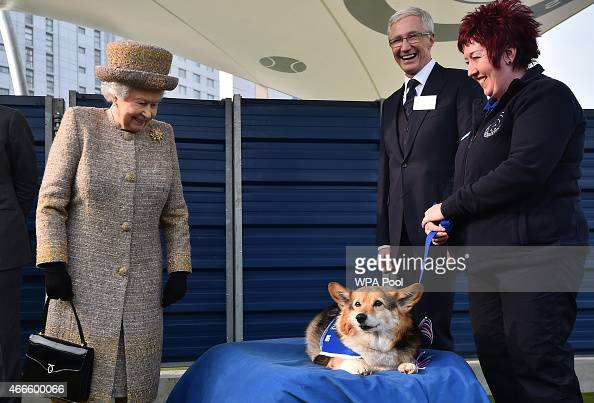 Britain's Queen Elizabeth II looks at a Corgi dog as British television presenter Paul O'Grady looks on during the opening of the new Mary Tealby dog...
